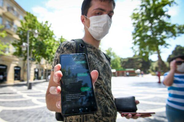 Молодой человек показывает смс-разрешение для выхода на улицу - Sputnik Азербайджан