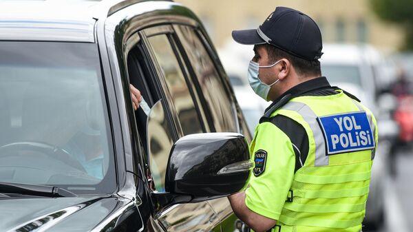 Сотрудник дорожной полиции проверяет разрешение водителя для выходы на улицу - Sputnik Азербайджан