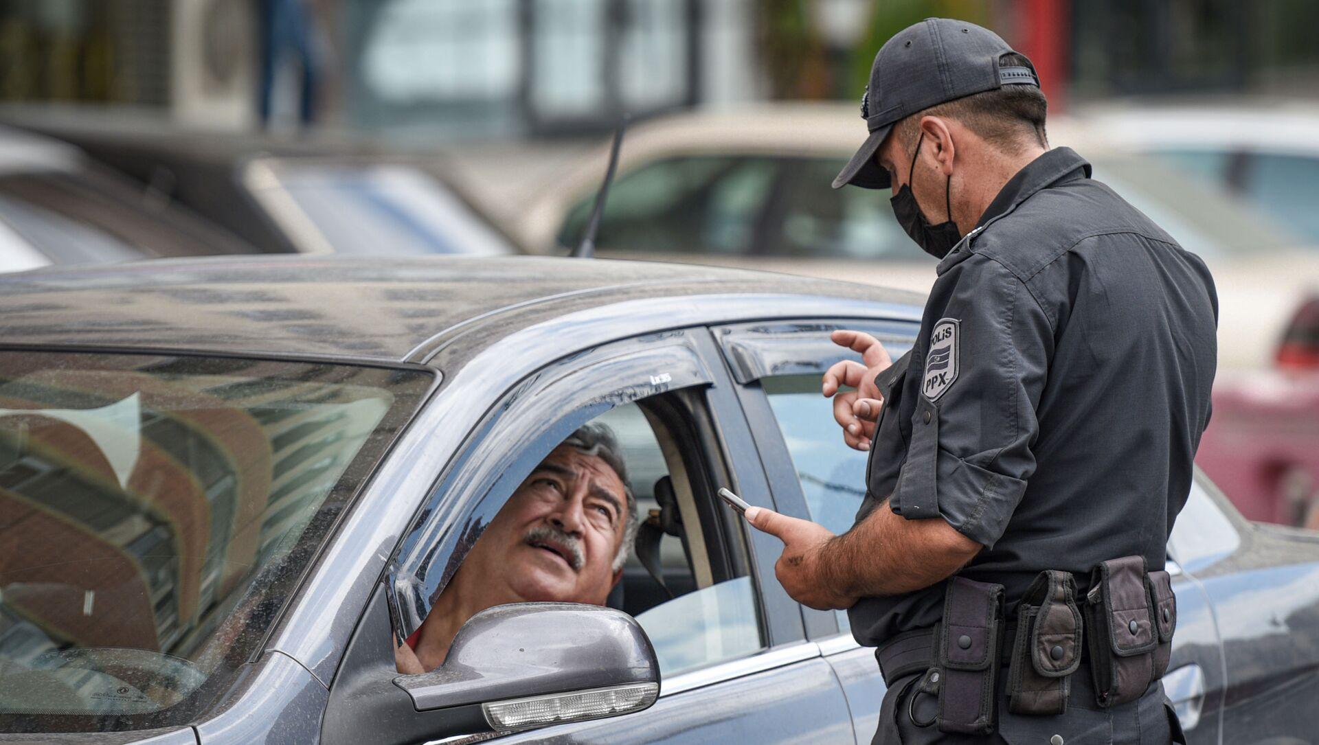 Сотрудник полиции проверяет разрешение водителя для выходы на улицу - Sputnik Азербайджан, 1920, 23.09.2021