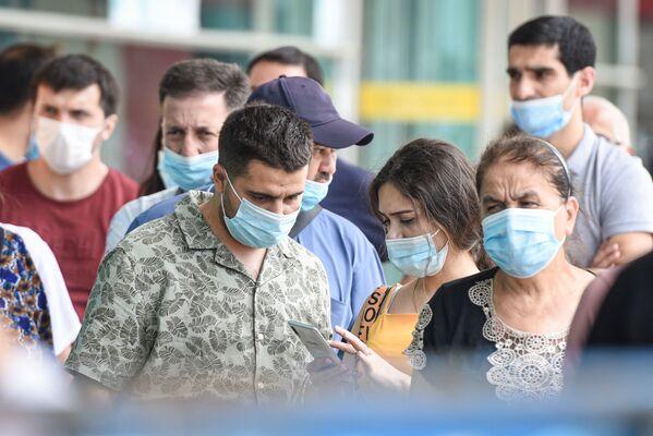 Люди в защитных масках на улице в Баку во время особого карантинного режима - Sputnik Азербайджан