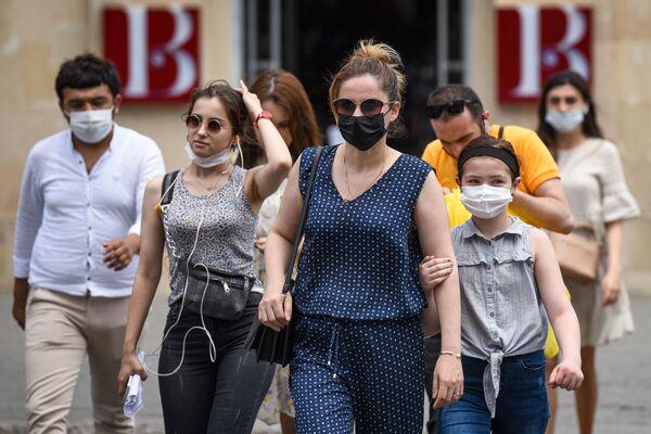 Люди в медицинских масках на улице в Баку во время особого карантинного режима - Sputnik Азербайджан
