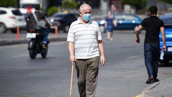 Мужчина в защитной маске на улице в Баку во время особого карантинного режима - Sputnik Azərbaycan