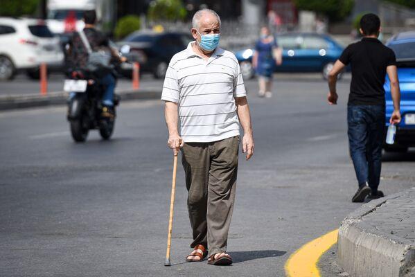 Мужчина в защитной маске на улице в Баку во время особого карантинного режима - Sputnik Азербайджан