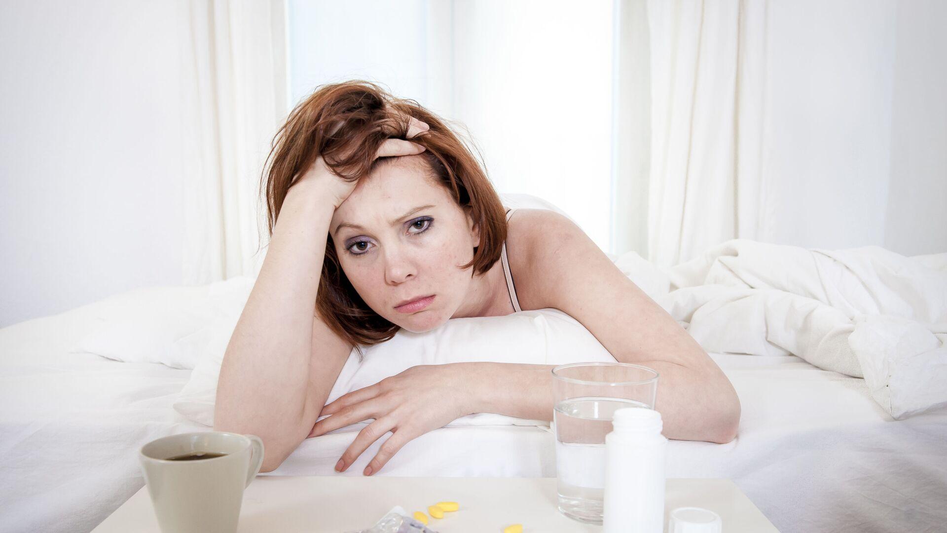 Болеющая девушка в постели с таблетками и чашкой кофе - Sputnik Azərbaycan, 1920, 05.09.2021