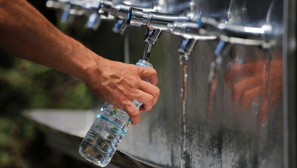 Мужчина наполняет бутылку водой, фото из архива - Sputnik Азербайджан