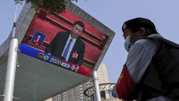 Охранник стоит на страже у экрана телевизора, на котором президент Китая Си Цзиньпин, фото из архива - Sputnik Азербайджан