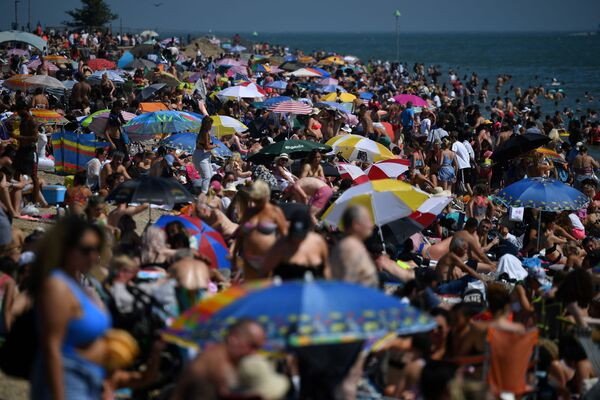 Отдыхающие на пляже Саутенд-он-Си на юго-востоке Англии через несколько дней после отмены карантина - Sputnik Азербайджан