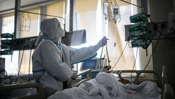 Медик проверяет капельницу у пациента в реанимации городской клинической больницы № 15 имени О. М. Филатова в Москве. - Sputnik Azərbaycan